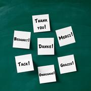 Sticky notes with thank you written in various languages on blac Stock Photos