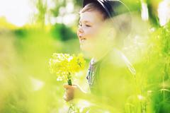smiling boy holding yellow flowers - stock photo