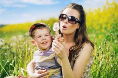 pretty young mother playing dandelions with son - stock photo