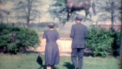 Old film older couple looking at a horse statue old fashion vintage lifestyle Stock Footage