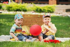 two little brothers playing on the balnket - stock photo