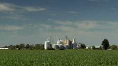 Driving by a cornfield with grain elevators in background Stock Footage