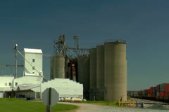 Train passing by grain elevators in rural Midwest farming area Stock Footage