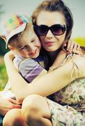 beautiful mom hugging her cute son - stock photo