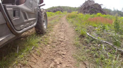 Low shot of a four wheeler traveling on dirt road Stock Footage