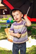 curious boy with big umbrella - stock photo
