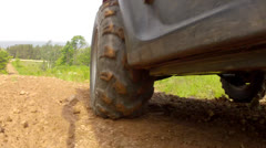 A low shot of a four wheeler traveling on a dirt road Stock Footage