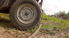 low shot of a tire on a four wheeler traveling on dirt road - stock footage