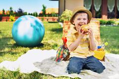 charming boy eating huge apple - stock photo