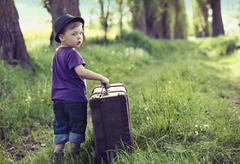 little man leaving home with huge luggage - stock photo