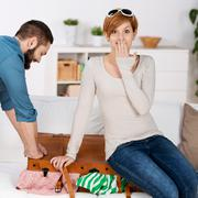 couple trying to close suitcase at home - stock photo