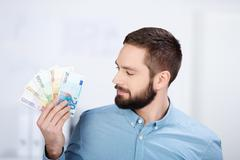 businessman holding looking on euro notes - stock photo