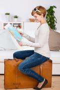 Woman looking at map while sitting on suitcase Stock Photos