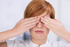 Businesswoman covering eyes with hands Stock Photos