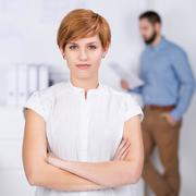 Businesswoman with coworker in background Stock Photos
