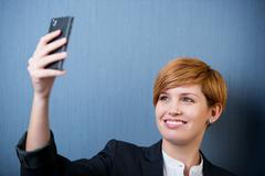 Woman taking self portrait with phone camera Stock Photos