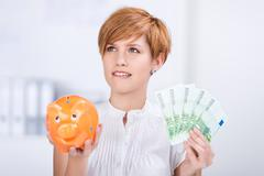 businesswoman holding euro notes and piggy bank - stock photo
