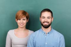 male and female students against chalkboard - stock photo