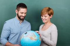 Teachers examining globe together against chalkboard Stock Photos