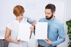 Businessman and businesswoman holding blank papers Stock Photos