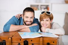 Couple with map leaning on suitcase in house Stock Photos
