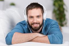 Young man lying on sofa while listening to music Stock Photos
