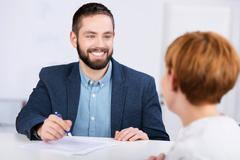 Man explaining documents to female co worker at desk Stock Photos