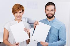Stock Photo of businessman and businesswoman holding blank papers