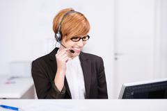 receptionist speaking on headphones - stock photo