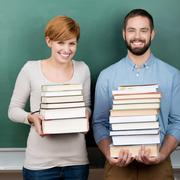 teachers with stack of books against chalkboard - stock photo