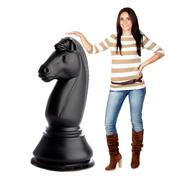 Beautiful brunette girl and a big chess knight Stock Photos