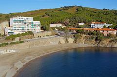 Calm mediterranean beach with apartment building Stock Photos