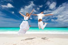wedding couple jumping on the beach - stock photo