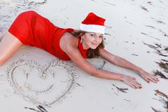 happy woman in santa hat on tropic beach - stock photo