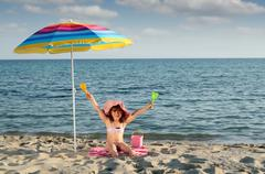 happy little girl with hands up sitting under sunshade on beach - stock photo