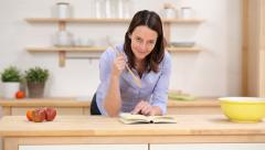 Woman baking in the kitchen reading the recipe Stock Footage