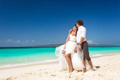 bride and groom  having fun on beach - stock photo