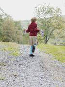 A rear view of a young girl jumping road on a gravel path in the country - stock photo
