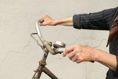 hands holding handlebar of a bicycle. - stock photo