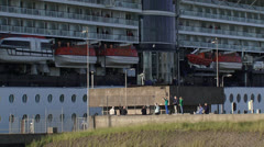 Cruise ship moves out of North Sea lock, people wave goodbye Stock Footage