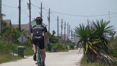 Professional cyclist riding away in a coastal neighborhood Stock Footage