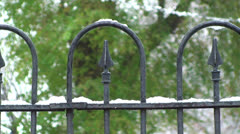 Snow falls on a wrought iron fence Stock Footage