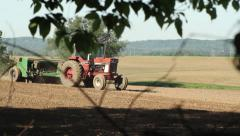 Small tractor traveling fast in a feild during planting season Stock Footage
