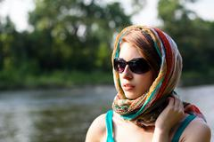 Beautiful young woman wearing sunglasses and a teal scarf near a river Stock Photos