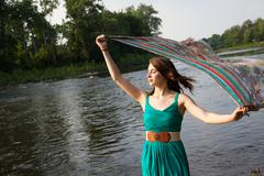 Beautiful girl holding scarf in breeze by river - stock photo