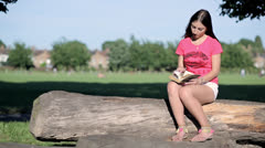 Woman sitting on a log reading a book Stock Footage