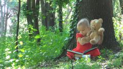 Child with Teddy Bear Toy Reading a Story Book, Girl Playing in Forest, Children Stock Footage