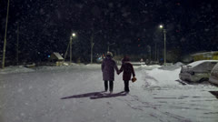 Mother and daughter on a snowy street at a Russian township in the winter Stock Footage