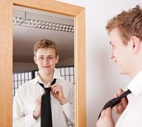 Stock Photo of young man binding his tie