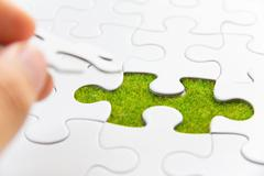 Hand embed missing puzzle piece into place - stock photo